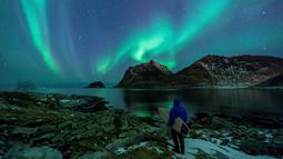 Seorang surfer melihat Cahaya Utara atau aurora borealis di Utakleiv, Norwegia utara (9/3). Cahaya kutub terbentuk dari interaksi medan magnet Bumi dengan lapisan terluar Matahari atau Korona. (AFP/Olivier Morin)