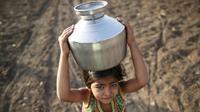 Seorang anak membawa kendi berisi air di Latur, India, (17/4). Akibat bencana kekeringan warga mengalami krisis air bersih yang melanda India. (REUTERS/Danish Siddiqui)