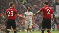 Bek Manchester United (MU) Luke Shaw dan Victor Lindelof (kanan) sukses menghentikan bintang Liverpool Mohamed Salah pada laga Liga Inggris di Old Trafford, Minggu (24/2/2019). (AFP/Oli Scarff)