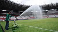 Pekerja menyemprot rumput lapangan Stadion Gelora Bung Karno pasca renovasi, Jakarta, Jumat (12/1). Rencananya, Stadion GBK akan diresmikan penggunaannya pasca renovasi oleh Presiden Joko Widodo, Minggu (14/1). (Liputan6.com/Helmi Fithriansyah)