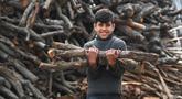 Seorang anak laki-laki menggotong kayu bakar di sebuah bengkel kerja di Damaskus, ibu kota Suriah, pada 23 November 2020. Warga Suriah mengumpulkan kayu bakar untuk menghadapi cuaca dingin. (Xinhua/Ammar Safarjalani)