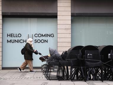 Seorang wanita berjalan di depan toko pakaian yang tutup di pusat kota di Munich, Jerman, Selasa (23/3/2021). Jerman memperpanjang tindakan pengunciannya sebulan lagi. (AP Photo/Matthias Schrader)