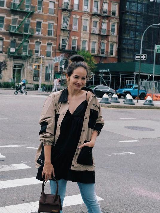 Berkunjung ke New York, street style Enzy Storia kali ini jatuh pada jaket dan dress hitam yang dipadu celana jeans. (Instagram/enzystoria).