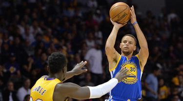 Pemain Golden State Warriors, Stephen Curry melepaskan tembakan saat dihadang pemain LA Lakers, Julius Randle (kiri) pada laga NBA preseason di Valley View Casino Center, San Dieg, Kamis (20/10/2016). (Reuters/Jake Roth-USA TODAY Sports)