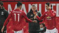 Striker Manchester United, Edinson Cavani (kanan) bersiap memasuki lapangan menggantikan striker Mason Greenwood dalam laga babak kelima Piala FA 2020/21 melawan West Ham di Old Trafford Stadium, Selasa (9/2/2021). Manchester United menang 1-0 (0-0) melalui extra time. (AFP/Michael Regan/Pool)