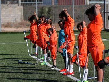 Anak-anak Palestina yang diamputasi melakukan pemanasan dalam sesi pelatihan sepak bola, yang diatur oleh Komite Palang Merah Internasional (ICRC) setelah pembatasan penyakit coronavirus (COVID-19) mereda, di Deir al-Balah di Jalur Gaza tengah (14/7/2020). (AFP/Mahmud Hams)