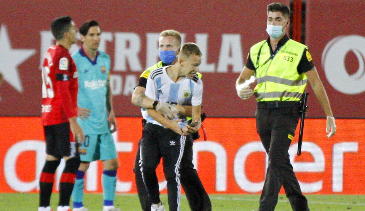 Petugas keamanan menangkap seorang fans yang nekat menerobos lapangan saat pertandingan antara Mallorca melawan Barcelona di Stadion Son Moix, Minggu (14/6/2020). Fans tersebut ingin berfoto dengan Lionel Messi. (AP/Francisco Ubilla)
