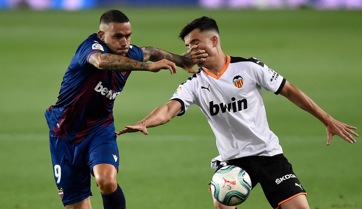 Bek Valencia, Hugo Guillamon, berebut bola dengan penyerang Levante, Roger Marti, pada laga pekan ke-28 Liga Spanyol di Stadion Mestalla, Sabtu (13/6/2020) dini hari WIB. Valencia bermain imbang 1-1 atas Levante. (AFP/Jose Jordan)