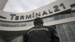 Seorang pria berdiri selama upacara peringatan di tempat penembakan massal di pusat perbelanjaan Terminal 21 Korat di Nakhon Ratchasima, Thailand, Senin, (10/2/2020). Sebanyak 26 orang tewas dan melukai puluhan lainnya akibat insiden tersebut. (AP Photo/Sakchai Lalit)