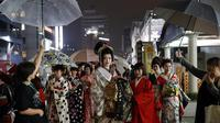 Sejumlah wanita Jepang berjalan di jalan setelah menghadiri peragaan busana kimono di Oita (18/10/2019). Sebutan lain untuk kimono adalah gofuku. Istilah gofuku mulanya dipakai untuk menyebut pakaian orang negara Dong Wu yang tiba di Jepang dari daratan China. (AP Photo/Christophe Ena)