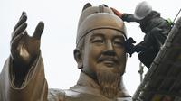 Pekerja membersihkan patung perunggu Raja Sejong di plaza Gwanghwamun di Seoul (9/4). Raja Sejong adalah penguasa Korea kedua yang mendapatkan gelar Raja Yang Agung atau Raja Besar setelah Raja Gwanggaeto dari Kerajaan Goguryeo. (AFP Photo/Jung Yeon-Je)