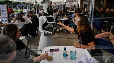 "Sebuah robot yang dikenal sebagai ""Alexia"" menyajikan minuman kepada pengunjung sebuah bar di alun-alun Plaza del Castillo, di Pamplona, Spanyol pada 5 Juni 2020. Robot tersebut digunakan untuk mengurangi penyebaran virus corona Covid-19. (AP Photo/Alvaro Barrientos)"