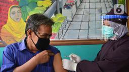 Seorang pedagang melakukan vaksinasi Covid-19  di Pasar Cisalak, Depok, Jawa Barat, Selasa (9/3/2021). Vaksinasi Covid-19 di empat pasar tradisional tersebut untuk mempercepat program vaksinasi yang digaungkan pemerintah. (merdeka.com/Arie Basuki)