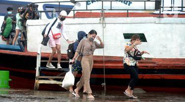 Wisatawan turun dari kapal tradisional usai perayaan malam pergantian Tahun Baru 2021 di Pelabuhan Kali Adem, Jakarta, Jumat (1/1/2021). Beberapa obyek wisata Kepulauan Seribu yang ditetapkan sebagai lokasi pengendalian ketat, adalah Pantai Sakura, Pantai Taman Arsa. (merdeka.com/Imam Buhori)