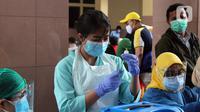 Vaksinator menyiapkan vaksin COVID-19 saat vaksinasi massal di Gedung Pemerintah Kota Tangerang, Banten, Kamis (25/2/2021). Vaksinasi ini dilaksanakan hingga satu minggu ke depan. (Liputan6.com/Angga Yuniar)