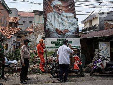 Petugas PPSU didampingi TNI dan Polri mencopot baliho Rizieq Shihab di Kawasan Kramat Pulo Dalam Senen, Jakarta, Rabu (25/11/2020). Pihak kelurahan, TNI dan Polri terus berupaya menurunkan baliho dan spanduk yang tidak berizin, termasuk salah satunya baliho Rizieq Shihab (Liputan6.com/Faizal Fanani)