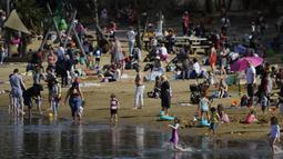 Orang-orang menikmati cuaca hangat di Ruislip Lido di London, Selasa (30/3/2021).  Suhu di beberapa bagian Inggris diperkirakan akan lebih hangat secara signifikan minggu ini karena keluarga dan teman berkumpul kembali dan kegiatan olahraga luar ruangan diizinkan untuk dilanjutkan di Inggris. (AP Ph