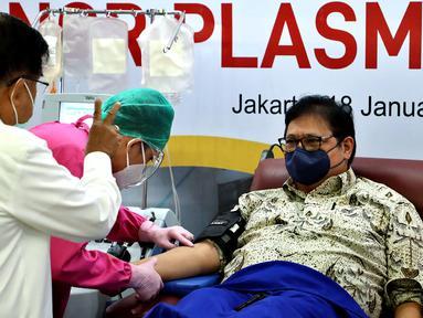 Ketua Umum PMI Jusuf Kalla (kiri) berbincang dengan Menko Perekonomian Airlangga Hartarto (kanan) yang sedang melakukan donor plasma konvalesen saat Pencanangan Gerakan Nasional Pendonor Plasma Konvalesen di Markas PMI, Jakarta, Senin (18/1/2021). (StaffJK/Ade Danhur)