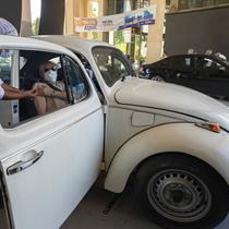 Seorang petugas kesehatan memberikan suntikan vaksin COVID-19 Sinovac kepada penumpang mobil selama program vaksinasi prioritas untuk lansia di lokasi drive-thru yang didirikan di tempat parkir stadion sepak bola Pacaembu, Sao Paulo, Brasil, Rabu (3/3/2021). (AP Photo/Andre Penner)