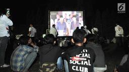 Para pendukung Capres dan Cawapres nomor urut 01 dan 02 saat nonton bareng Debat Perdana Pilpres di kawasan Gedung Bidakara, Jakarta, Kamis (17/1). Mereka menonton lesehan dengan layar tancap yang disediakan warga sekitar. (merdeka.com/Iqbal S Nugroho)