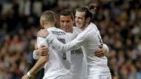 Gareth Bale dan Cristiano Ronaldo berpelukan setelah Karim Benzema mencetak gol ke gawang Sevilla, Minggu (20/3/2016). (EPA/Jason Powell)