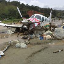 Sebuah pesawat twin otter rusak pasca terseret banjir bandang dan menutupi lapangan terbang di Kabupaten Sentani, Jayapura, (17/3). Banjir bandang Sentani menewaskan 70 orang dan puluhan luka-luka. (AFP/Netty Dharma Somba)