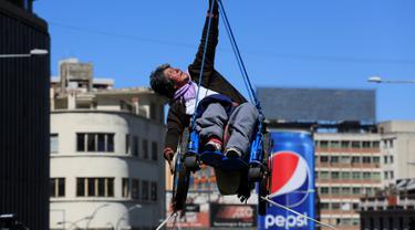 Seorang wanita penyandang cacat menggantungkan diri saat mengelar aksi menuntut kesejahteraan di sebuah jembatan di La Paz, Bolivia (3/5). Aksi ini menuntut pemerintah Bolivia untuk memberikan subsidi bulanan. (REUTERS/David Mercado)