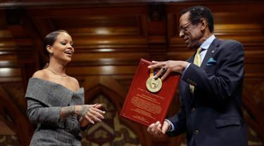 Penyanyi Rihanna (kiri) saat menerima penghargaan dari direktur Harvard Foundation, Allen Counter di Cambridge, AS, (28/2). Rihanna mendapat penghargaan Humanity of the Year Award 2017 dari Harvard University. (AP Photo/Steven Senne)