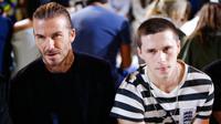 Mantan pesepakbola, David Beckham dan putranya Brooklyn tampak duduk di barisan depan fashion show koleksi musim panas 2018 Victoria Beckham dalam pagelaran New York fashion Week, Minggu (10/9). (EDUARDO MUNOZ ALVAREZ / AFP)