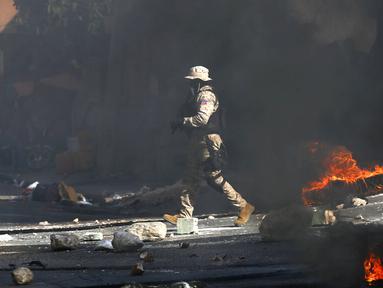 Polisi membersihkan jalan dari batu dan ban yang dibakar oleh pengunjuk rasa yang marah dengan meningkatnya kekerasan di lingkungan Lalue, Port-au-Prince, Haiti, Rabu (14/7/2021). Presiden Haiti Jovenel Moise dibunuh pada 7 Juli. (AP Photo/Fernando Llano)