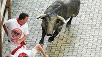 Dua orang peserta berusaha menghindar dari serudukan banteng  selama hari ketiga Festival San Fermin di Pamplona, Spanyol utara, (9/7). (AFP Photo/Jose Jordan)