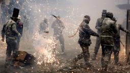 Peserta mengikuti perang petasan selama festival Els Enfarinats di kota Ibi dekat Alicante, Spanyol (28/12). Selama sekitar 200 tahun penduduk Ibi setiap tahun merayakan dengan pertempuran menggunakan tepung, telur, dan petasan. (AP Photo/Alberto Saiz)