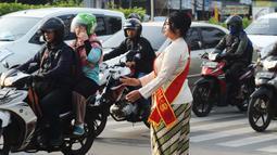 Personel Polisi Wanita (Polwan) Polres Jakarta Timur mengenakan pakaian kebaya saat mengatur arus lalu lintas di Jalan Otista Raya, Jatinegara, Jumat (20/4). Para polwan itu juga mengenakan selempang bertulisan Polres Jaktim. (Merdeka.com/Imam Buhori)