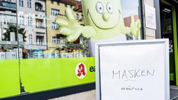 """Papan bertuliskan """"masker tersedia"""" terlihat di luar apotek di Berlin pada 29 April 2020. Berlin mewajibkan penggunaan masker di seluruh gerai usaha pada Rabu (29/4), sementara kewajiban mengenakan masker sudah diberlakukan di seluruh moda transportasi publik sejak Senin (27/4). (Xinhua/Binh Truong"""