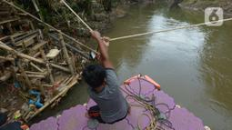 Seorang anak menggunakan perahu eretan di sungai Ciliwung, Jakarta, Selasa (3/11/2020). Perahu eretan di sungai Ciliwung masih bertahan sebagai penghubung Jakarta Timur dan Jakarta Selatan Selatan. (merdeka.com/Imam Buhori)