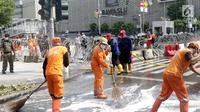 Pasukan oranye membersihkan sisa residu gas air mata dari badan jalan MH Thamrin dekat Gedung Bawaslu, Jakarta, Kamis (23/5/2019). Sebelumnya, aksi unjuk rasa yang dilakukan massa pada Rabu (22/5) berakhir ricuh. (Liputan6.com/Helmi Fithriansyah)