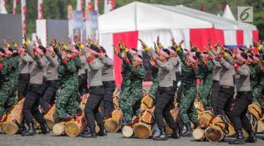 Prajurit TNI dan Polri berkolaborasi memainkan rampak gendang dalam HUT ke-73 Bhayangkara di Monas, Jakarta, Rabu (10/7/2019). HUT Bhayangkara ke-73 ini bertemakan 'Dengan semangat Promoter, pengabdian Polri, untuk masyarakat, bangsa, dan negara. (Liputan6.com/Faizal Fanani)