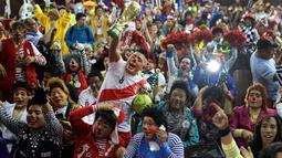 Sejumlah badut bersorak merayakan Hari Badut nasional di Lima, Peru, Jumat (25/5). Ratusan badut profesional dengan mengenakan kostum beraneka warna-warni, wig, dan wajah yang dicat, berpartisipasi dalam pawai di jalan kota Lima. (AP Photo/Martin Mejia)