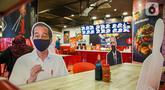 Banner bergambar karakter Presiden Joko Widodo terlihat di sebuah Restoran Hulu Hulu, Mall Kuningan City, Jakarta, Senin (1/3/2021). Banner bergambar tersebut berguna untuk pembatas bagi pengunjung yang makan di tempat saat pandemi.(Liputan6.com/Faizal Fanani)