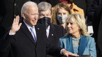 Presiden AS terpilih Joe Biden didampingi istri  Jill Biden saat dilantik oleh Ketua Mahkamah Agung John Roberts di US Capitol di Washington, Rabu (21/1/2021). Biden kini resmi menjabat sebagai Presiden ke-46 Amerika Serikat. (AP Photo/Andrew Harnik)