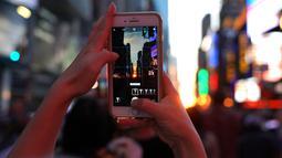 Seorang wanita mengambil gambar fenomena Manhattanhenge, dimana matahari terbenam sejajar tepat dengan jalan, di Times Square, New York City, Kamis (12/7). Manhattanhenge dimana saat matahari terbenam sejajar dengan jalan. (AFP/TIMOTHY A. CLARY)