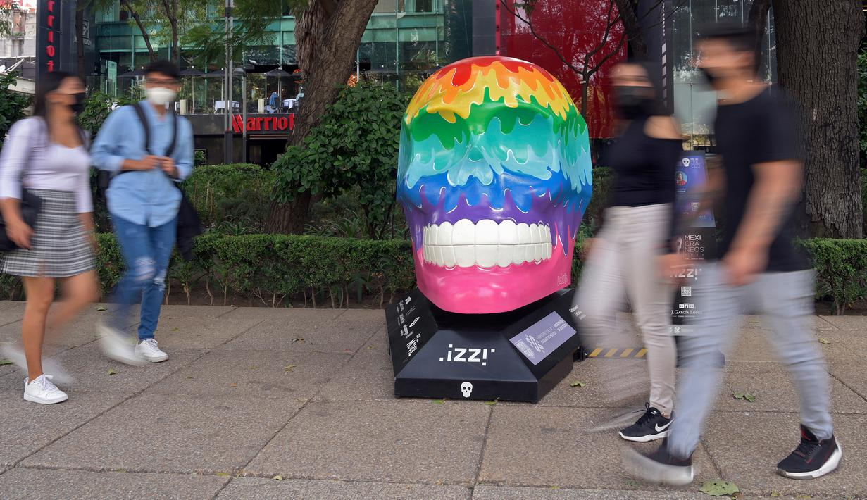 "Orang-orang melewati tengkorak yang dihias selama pameran edisi keempat ""Mexicraneos"" (Mexisculls) di Reforma Avenue, Mexico City pada 23 Oktober 2020. Instalasi sebanyak 55 tengkorak berbagai warna tersebut menghiasi jalanan sebagai bagian dari perayaan Day of the Dead. (ALFREDO ESTRELLA/AFP)"