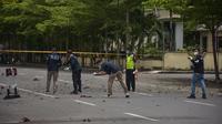 Polisi forensik memeriksa tempat kejadian setelah diduga bom meledak di dekat sebuah gereja di Makassar (28/3/2021). Sembilan orang terluka akibat kejadian tersebut. Empat di antaranya adalah jemaat gereja. (AFP/Indra Abriyanto)