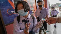 Guru memberikan pelindung wajah kepada seorang siswa di Samkhok School di Pathum Thani, Bangkok, Rabu (1/7/2020). Thailand telah memulai fase kelima relaksasi pembatasan covid-19 yang memungkinkan kembali dibukanya sekolah-sekolah setelah ditutup sejak Maret lalu. (AP/Sakchai Lalit)