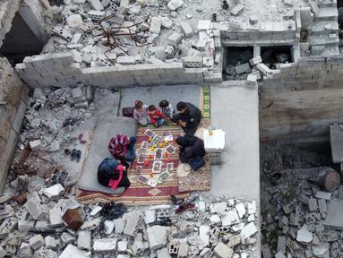 Keluarga Tareq Abu Ziad menunggu waktu berbuka puasa di tengah reruntuhan rumah mereka yang hancur setelah serangan militer pasukan pemerintah dan sekutunya di Kota Ariha, Provinsi Idlib, Suriah, Senin (4/5/2020). Muslim Suriah melewati Ramadan tahun ini masih dalam kondisi perang. (AAREF WATAD/AFP)
