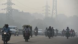 Kendaraan bermotor menembus kabut asap pekat yang menyelimuti jalan di New Delhi, Selasa (12/11/2019). Kabut asap kembali menyelimuti ibu kota India setelah akhir pekan dengan udara cerah dan cuaca yang lebih baik. (Photo by Money SHARMA / AFP)
