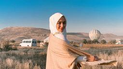 Anggunnya Citra Kirana mengenakan hijab dan dress panjang berwarna putih dipadu dengan syal krem dengan latar belakang balon udara dan padang ilalang di Cappadocia, Turki. (Liputan6.com/IG/@citraciki)