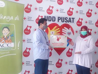 Kepala Unit Usaha SyariahACC Wisnu Wardhana (kiri) menyerahkan secara simbolis bantuan donor plasma kepada Kepala Unit Donor Darah PMI Ria Syafitri (kanan) di Jakarta Kamis (04/02/2021). (Liputan6.com/Pool)