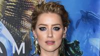 """Ekspresi Amber Heard saat menghadiri premier film terbarunya, """"Aquaman"""" di Los Angeles, California, AS (12/12). Amber Heard tampil seksi dengan gaun jaring-jaring menerawang hijau. (AP Photo/ Jordan Strauss)"""