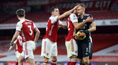 Para pemain Arsenal merayakan keberhasilan kiper Bernd Leno usai menggagalkan eksekusi penalti gelandang Chelsea, Jorginho, dalam laga lanjutan Liga Inggris 2020/21 pekan ke-15 di Emirates Stadium, London, Sabtu (26/12/2020). Arsenal menang 3-1 atas Chelsea. (AFP/Julian Finney/Pool)